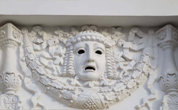 plaster mask on the wall of the theater. - tragedy mask stock photos and pictures