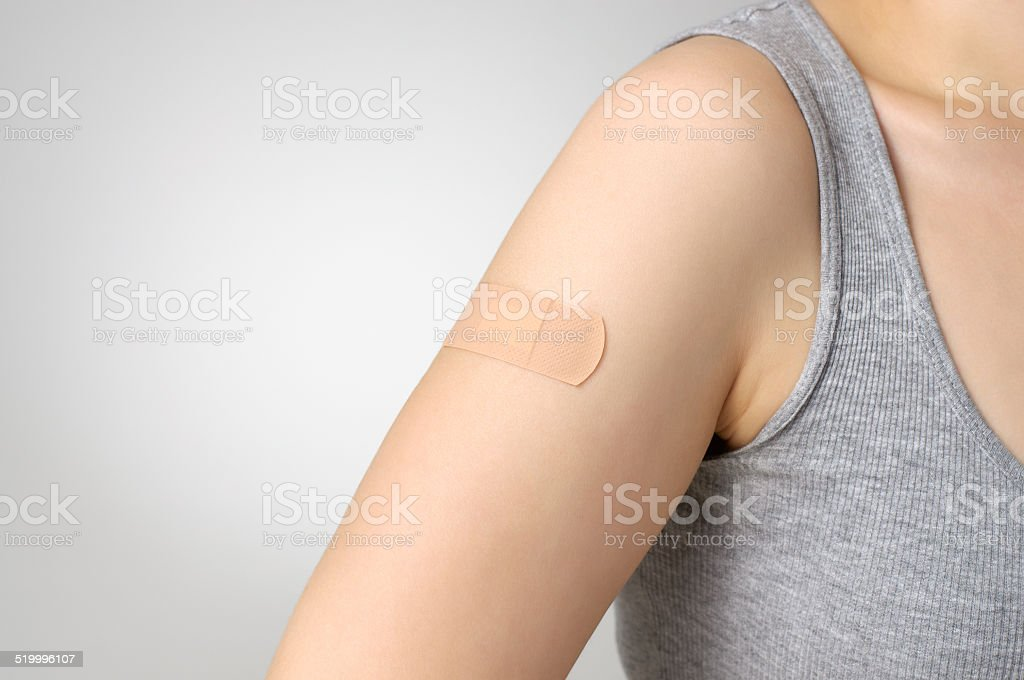 Plaster on female arm stock photo