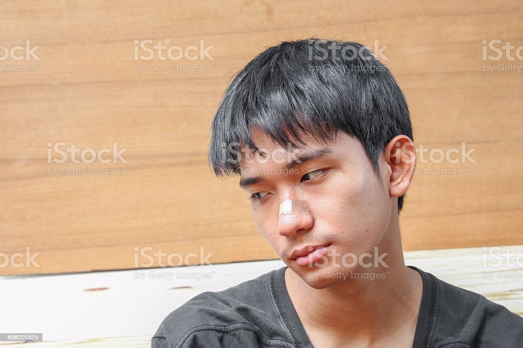 Plaster on young man  injury wound nose stock photo