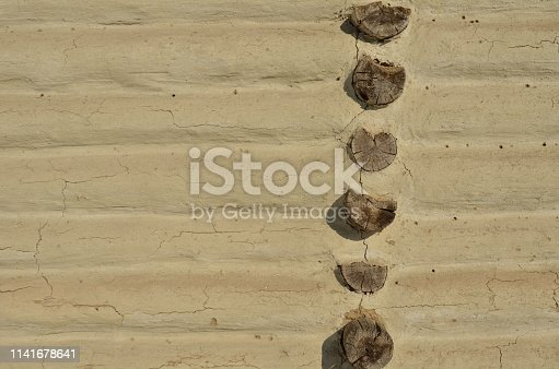 Fragment of the rustic house wall made of wooden beams covered with white adobe plaster. Abstract. Background.