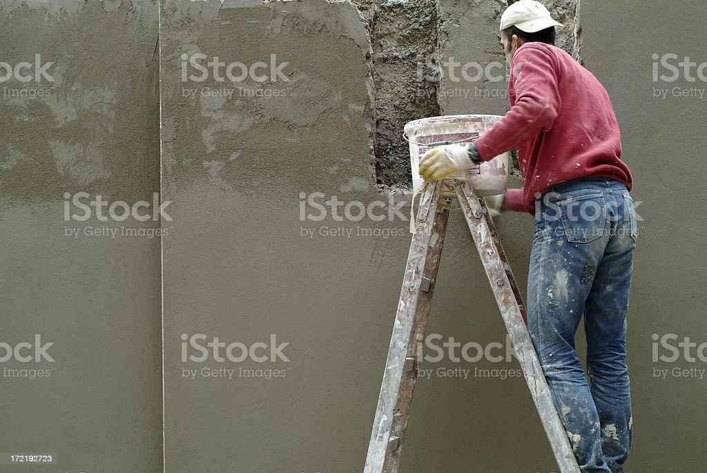 Plasterer at work on ladder royalty-free stock photo