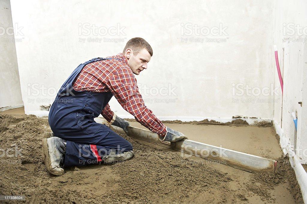 Plasterer concrete worker at floor work royalty-free stock photo