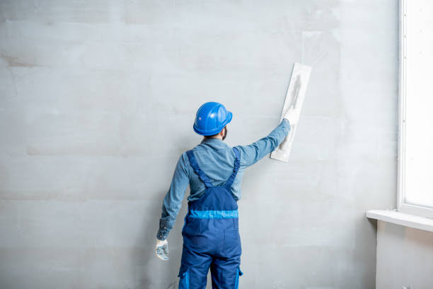 Plasterer working indoors Plasterer in blue working uniform plastering the wall indoors plaster stock pictures, royalty-free photos & images