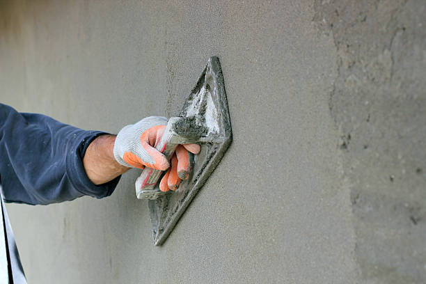 Plastering A Wall Man's hand plastering a wall with trowel. Selective focus. plaster stock pictures, royalty-free photos & images
