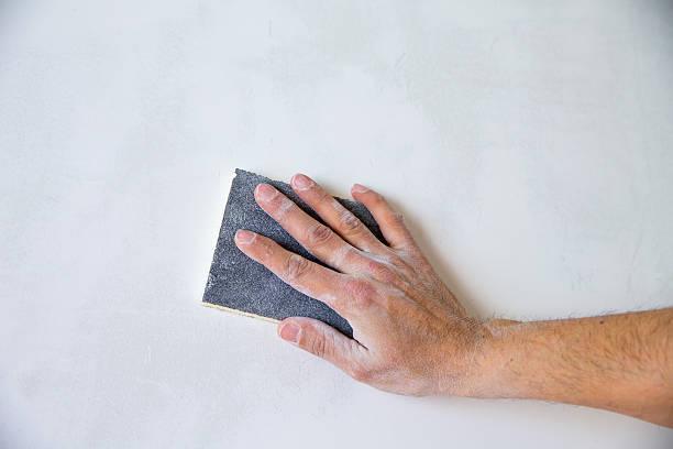 plastering mann hand geschmirgelt der verputz - schmirgelmaschine stock-fotos und bilder