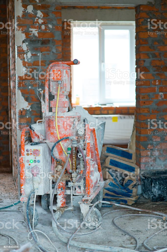 plastering pump Machine for Plastering Walls efficiently work Building of an apartment house stock photo