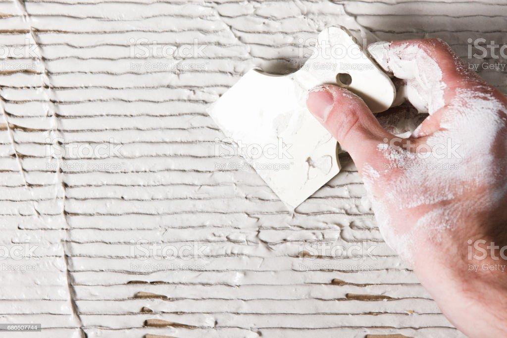 Plastering work. Hand with spatula spread stucco zbiór zdjęć royalty-free