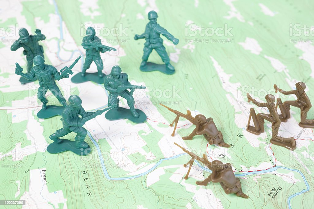 Plastic Army Men Fighting Battle on Topographic Map Arial View stock photo