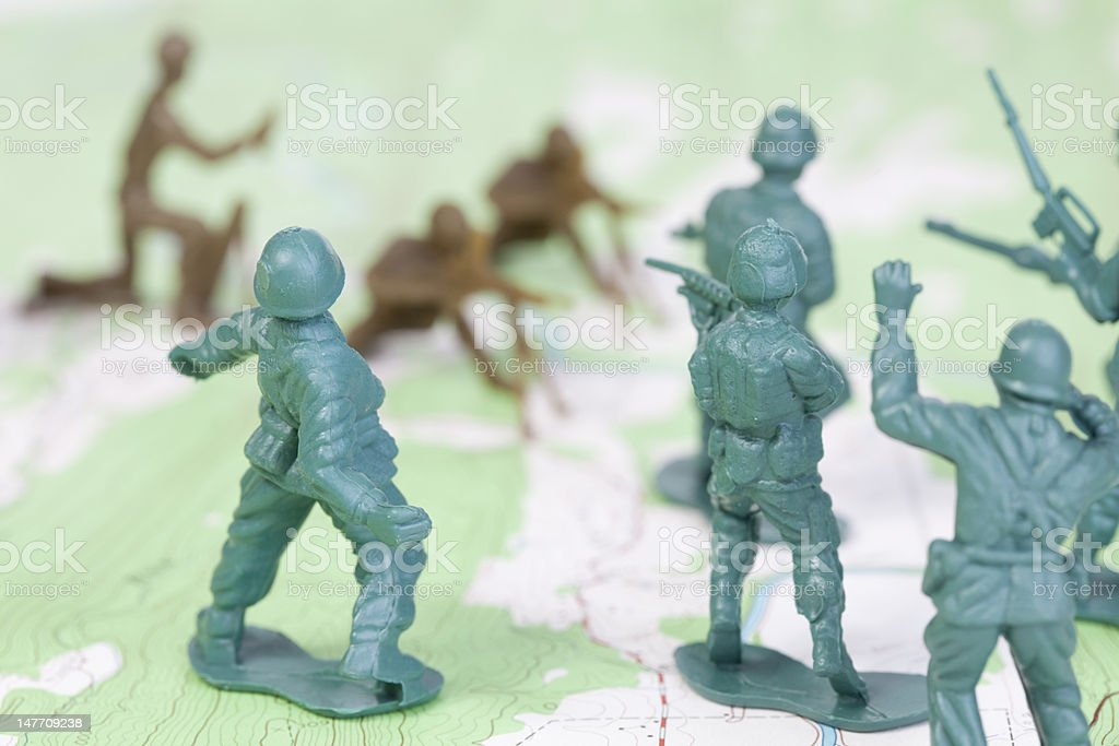 Plastic Army Men Fighting Battle on Topographic Map Throwing Grenade stock photo