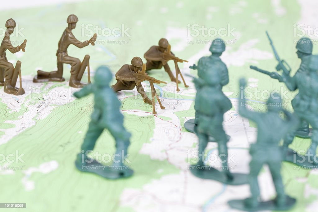 Plastic Army Men Fighting on Topographic Map Opposing Sides War stock photo