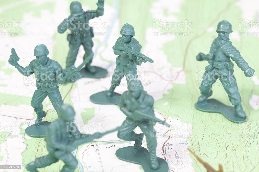 Plastic Army Men Fighting on Topographic Map. stock photo