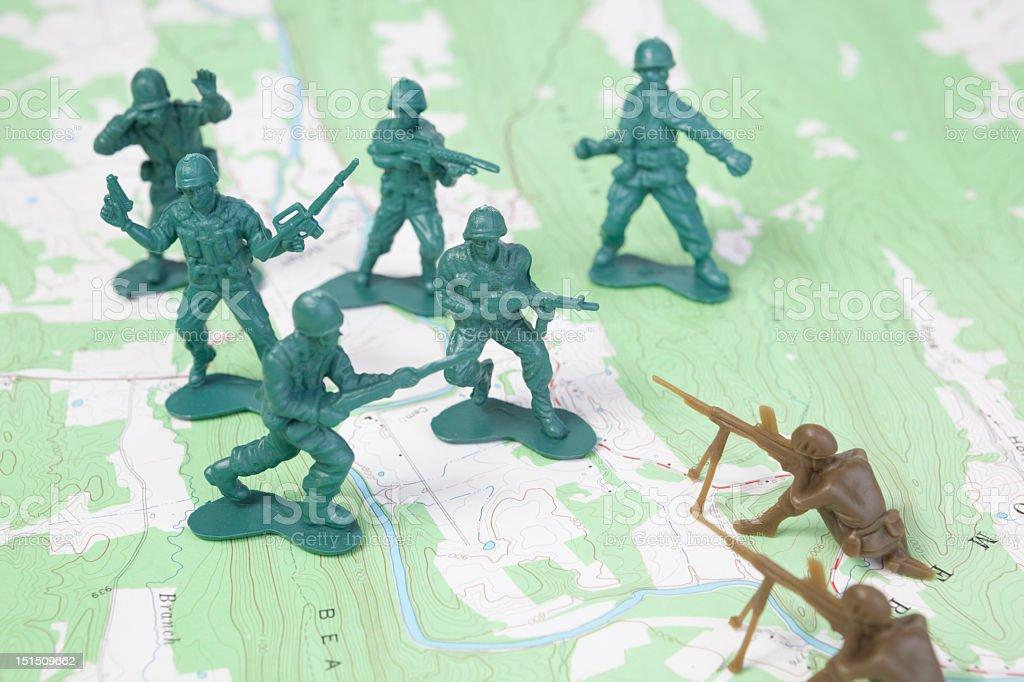 Plastic Army Men Fighting on Topographic Map stock photo