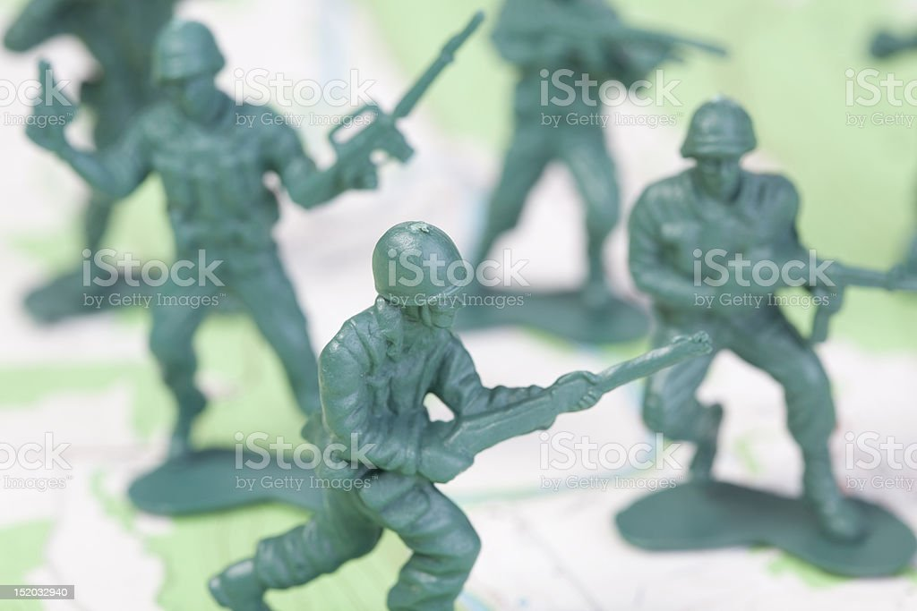 Plastic Army Men Fighting on Topographic Map Squad Attacks stock photo