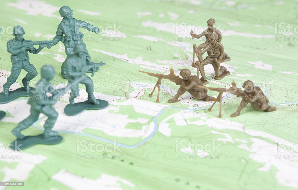 Plastic Army Men Fighting on Topographic Map Two Armies Battle stock photo