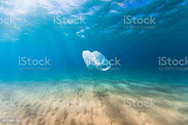 A plastic bag drifts in the clear blue ocean as a result of human pollution. Perfect for ocean conservation theme. (This bag was collected and taken out of the ocean)