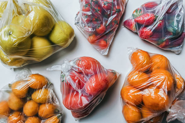Plastic bags full of fruits and vegetables. Climate change concept stock photo