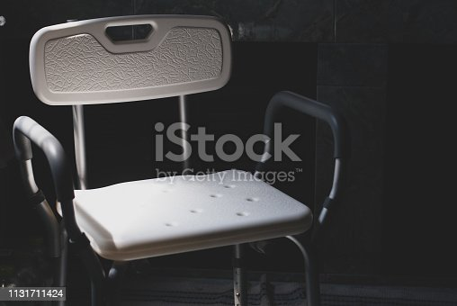 Plastic bathing chair for elder or disabled people showering put in dark letting light come from left side