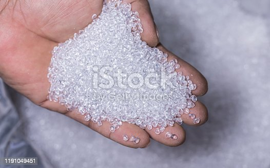 hands holding a pile of plastic pellets, Plastic beads for factory