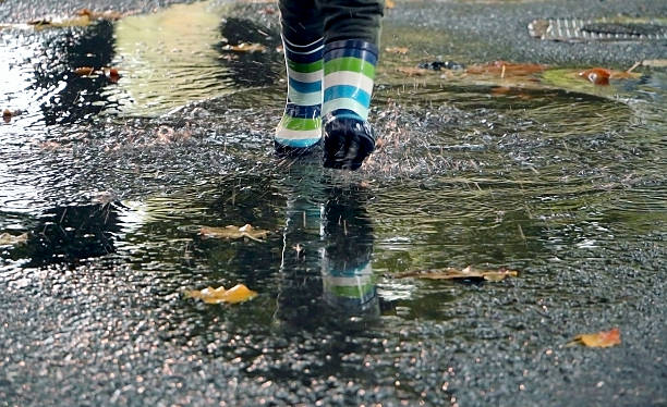 Plastic boots running through the puddle in autumn – Foto