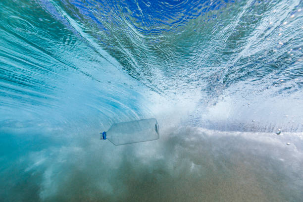 Plastic bottle behind a breaking wave stock photo