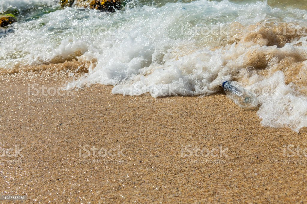 Plastic bottle being washed up in a wave. stock photo