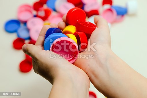 Hand with multicolored plastic bottle caps, studio shot, white background, recycle theme, circle.