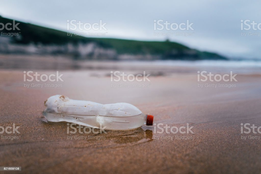 Botella de plástico en la playa - contaminación. - foto de stock