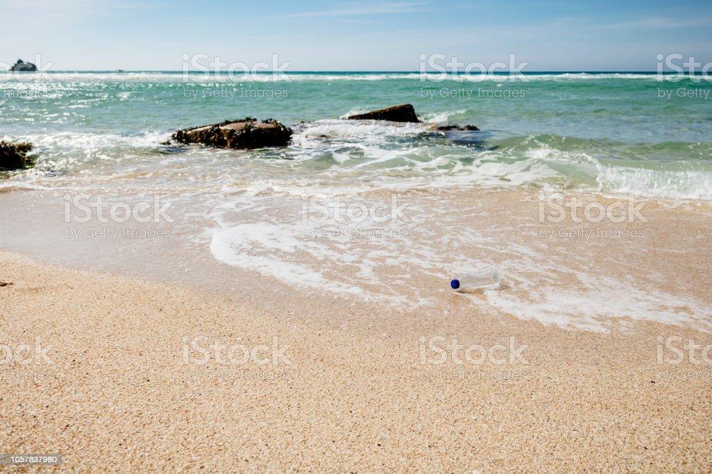 Plastic bottle on pristine beach. stock photo