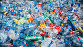 Stack of crushed colorful plastic bottles background waiting for recycle