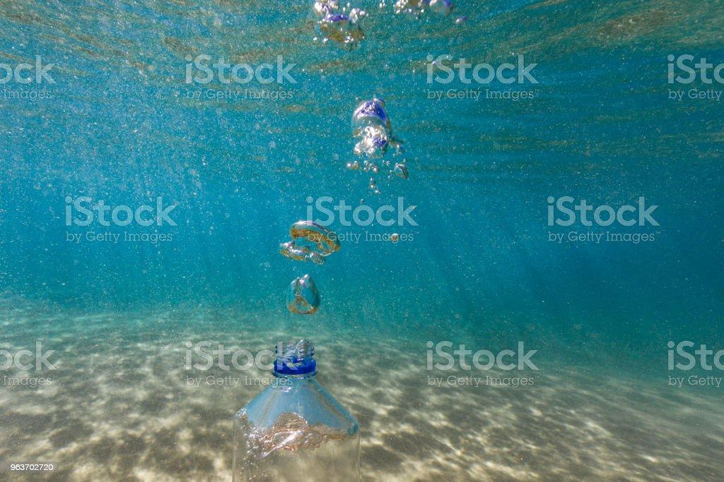 Plastic bottle sinking in the ocean stock photo