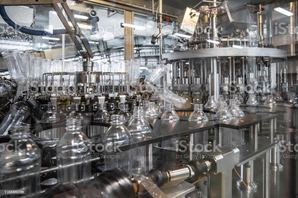 Plastic bottles inside industrial machine conveyor line or belt...