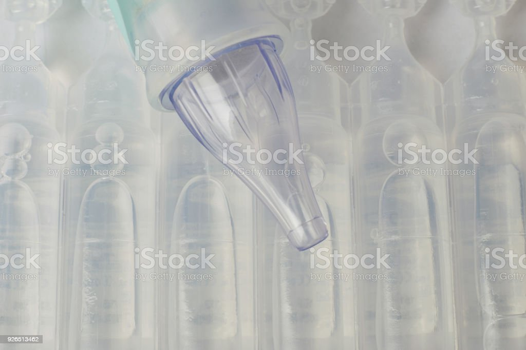 Plastic bottles of serum saline and a device of pulling out the mucus from the nose. stock photo