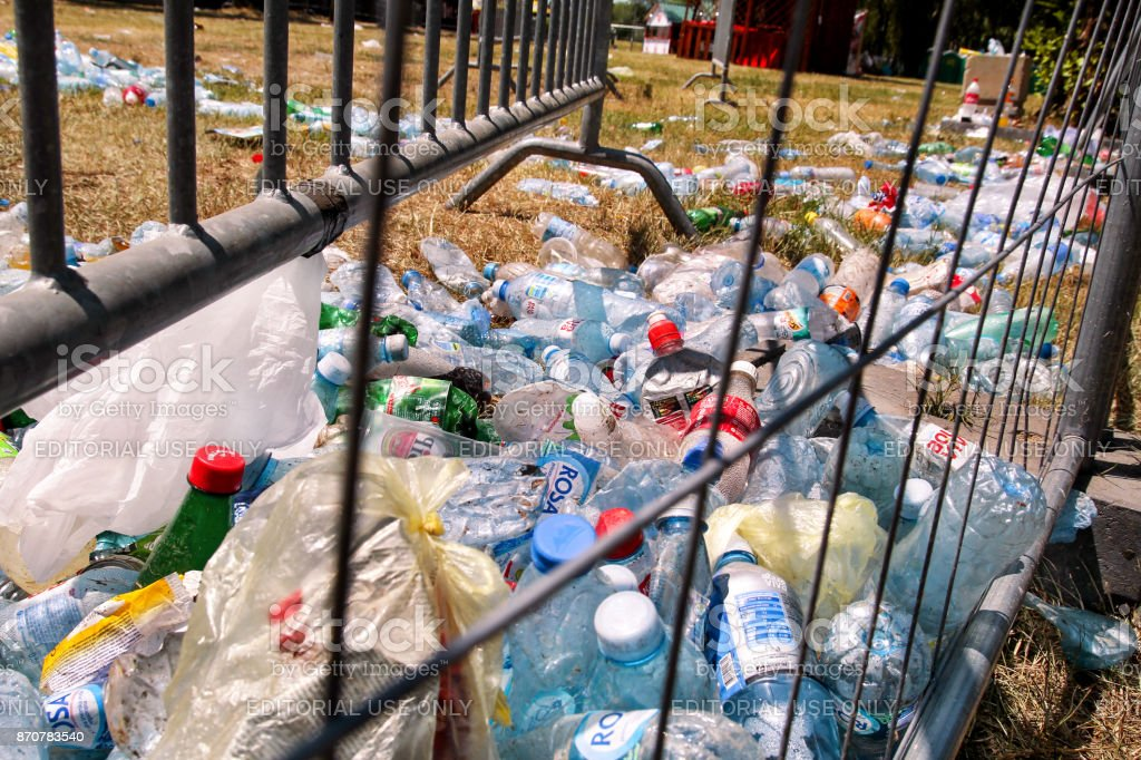 Plastic bottles tossed by the metal fence. Used empty pet bottles...