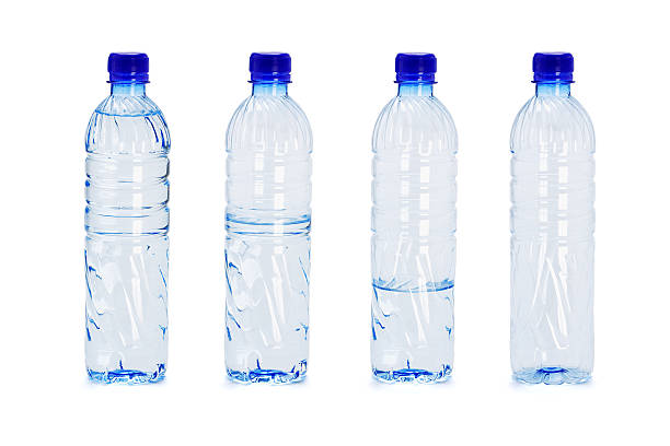 Plastic bottles with different water levels inside stock photo