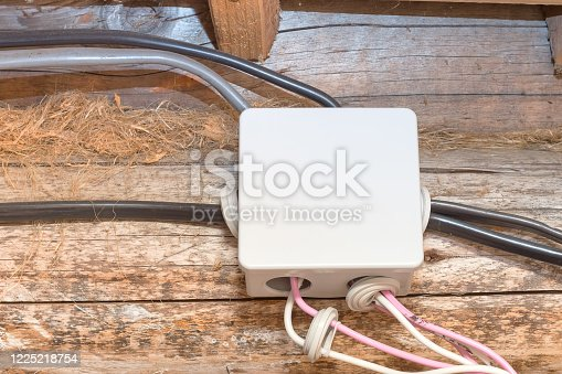 istock Plastic box of electrical wiring distributor in a wooden house. 1225218754