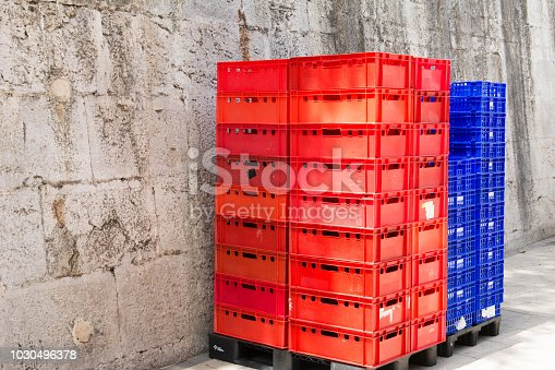 Stacked Red and blue empty plastic crates in shade outdoors