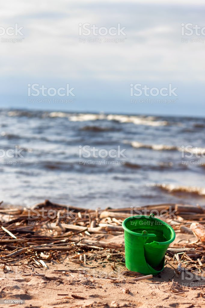 Plastic bucket on beach stock photo