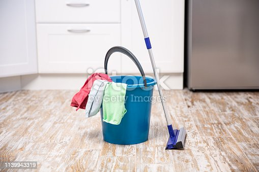 istock Plastic bucket with cleaning supplies in home 1139943319