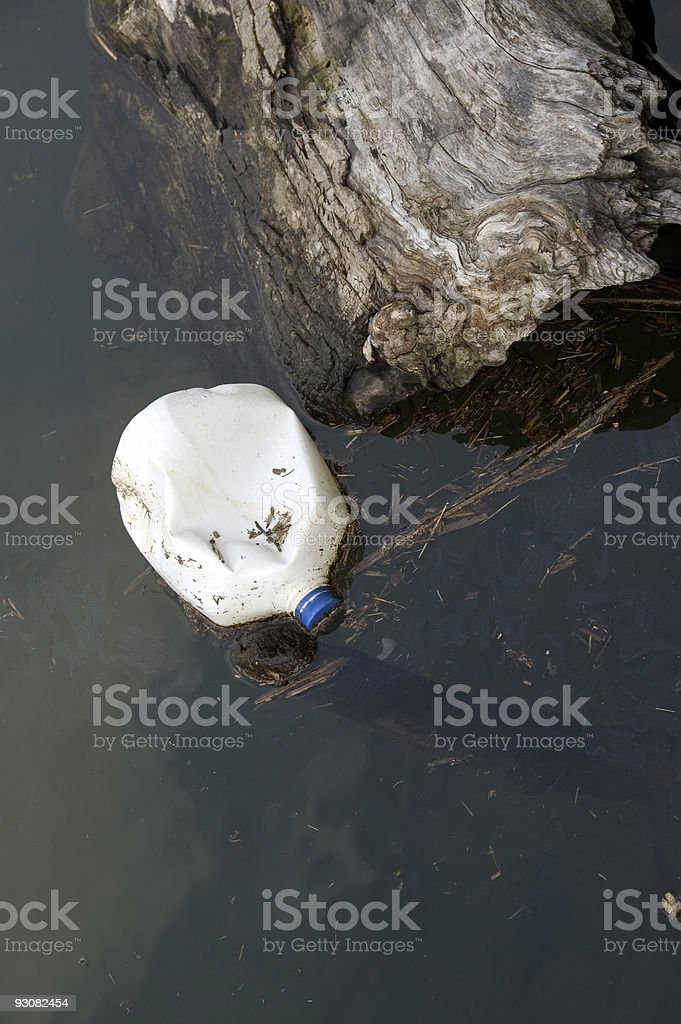Plastic can and oil spill on the lake royalty-free stock photo