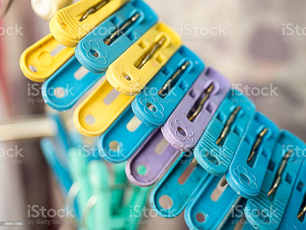 Plastic color clothespin hanging on rope stock photo