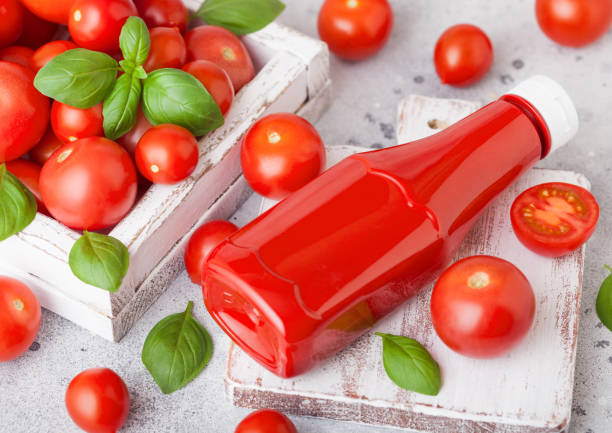 Plastic container with tomato ketchup sauce with raw tomatoes on kitchen stone background. Plastic container with tomato ketchup sauce with raw tomatoes on kitchen background. ketchup stock pictures, royalty-free photos & images