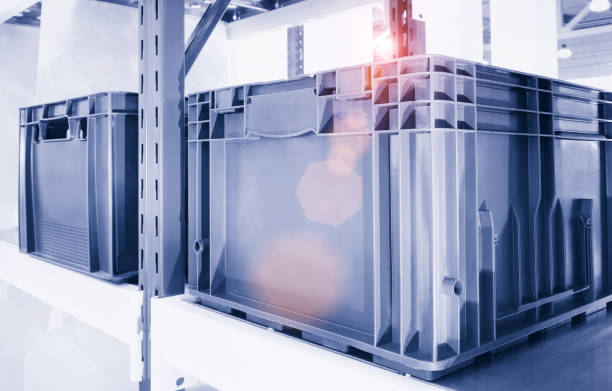 plastic containers on the modern warehouse for piece small storage of goods - metal robot in logistic factory foto e immagini stock