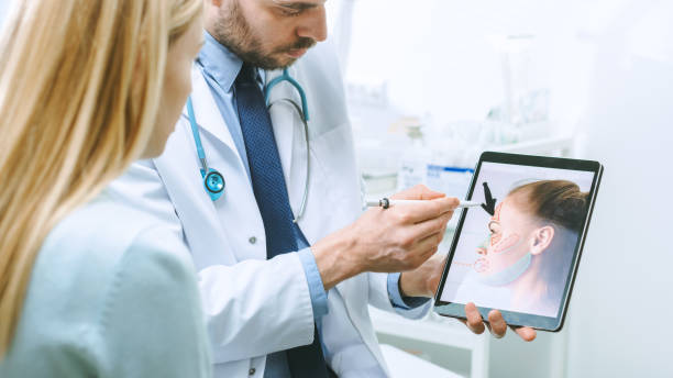 plastic / cosmetic surgeon consults woman about facial lift surgery, he points at digital tablet computer screen showing types of facelift, forehead lift and nose correcting procedures available. - plastica foto e immagini stock