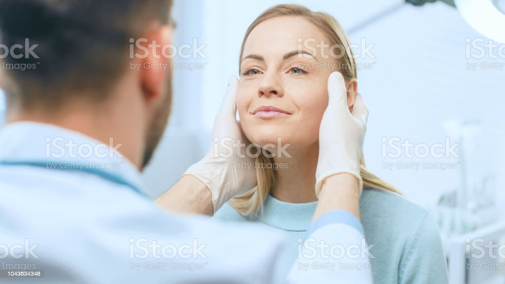 Plastic / Cosmetic Surgeon Examines Beautiful Woman's Face, Touches it with Gloved Hands, Inspecting Healed Face after Plastic Surgery with Amazing Results. - Foto stock royalty-free di Accudire