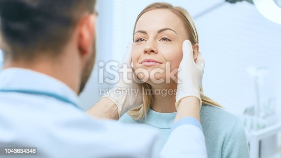 istock Plastic / Cosmetic Surgeon Examines Beautiful Woman's Face, Touches it with Gloved Hands, Inspecting Healed Face after Plastic Surgery with Amazing Results. 1043634348