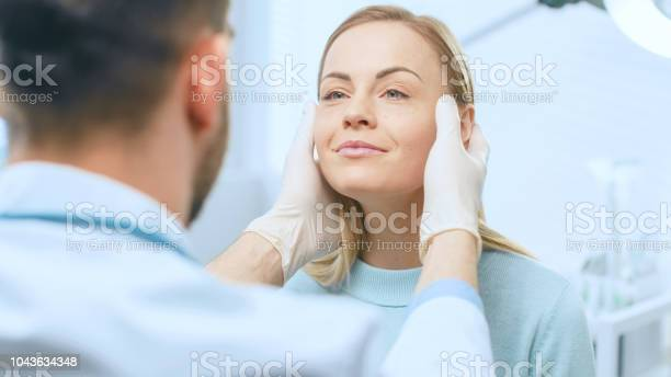 Plastic cosmetic surgeon examines beautiful womans face touches it picture id1043634348?b=1&k=6&m=1043634348&s=612x612&h=m6e1mpqlelpajbuthxwle5luab6piqcubexurelsyoo=