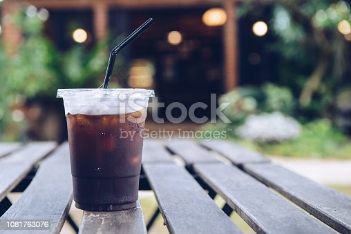 A plastic cup of iced coffee on the wooden table.