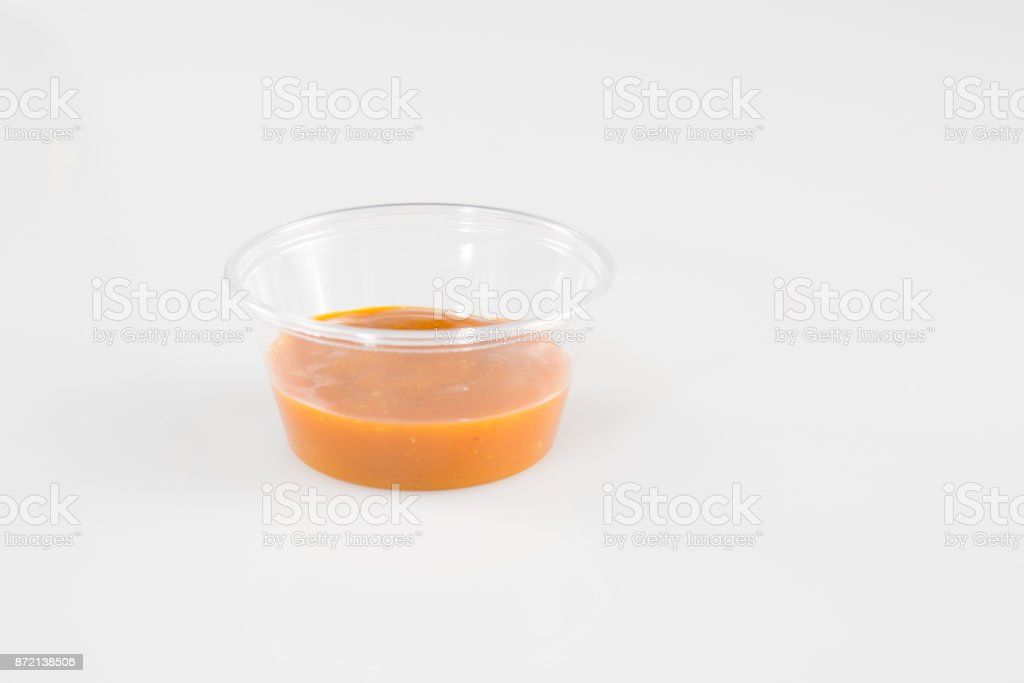 plastic cup sauce Relish mustard ketchup and mayonnaise condiments in clear containers on white background stock photo