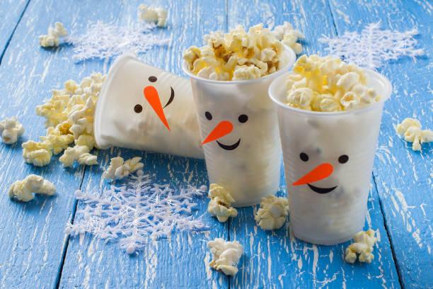 plastic cups in the form of snowmen with popcorn - diy xmas stock-fotos und bilder
