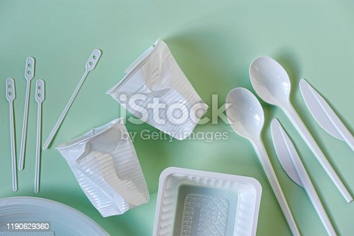 Two smashed white plastic coffee cups, spoons, knives, stirrers, plate and box on a light green background. Zero waste, plastic free, stop pollution, ecological concept.